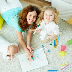 mere avec ses filles qui dessinent sur un tapis